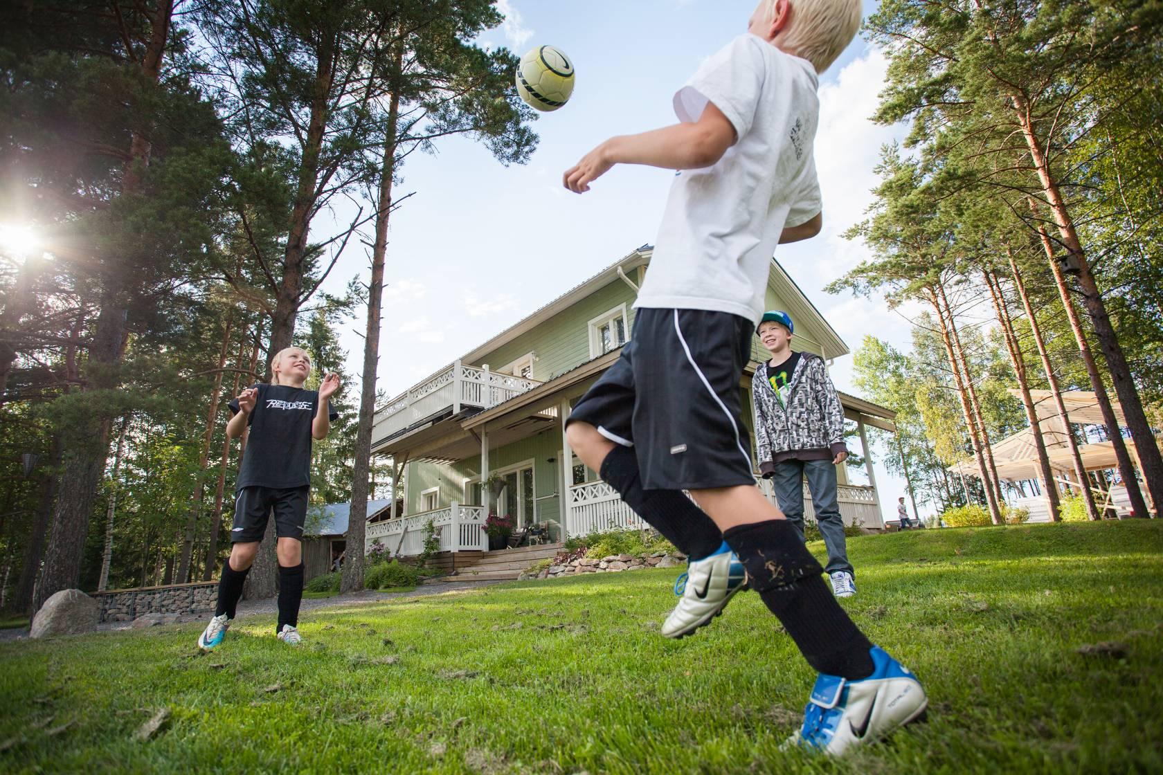 Pojat potkivat jalkapalloa omakotitalon pihalla