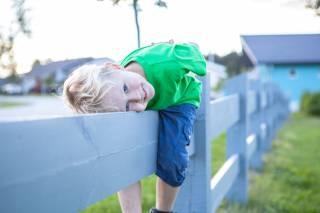Poika istuu aidalla omakotitalojen pihassa