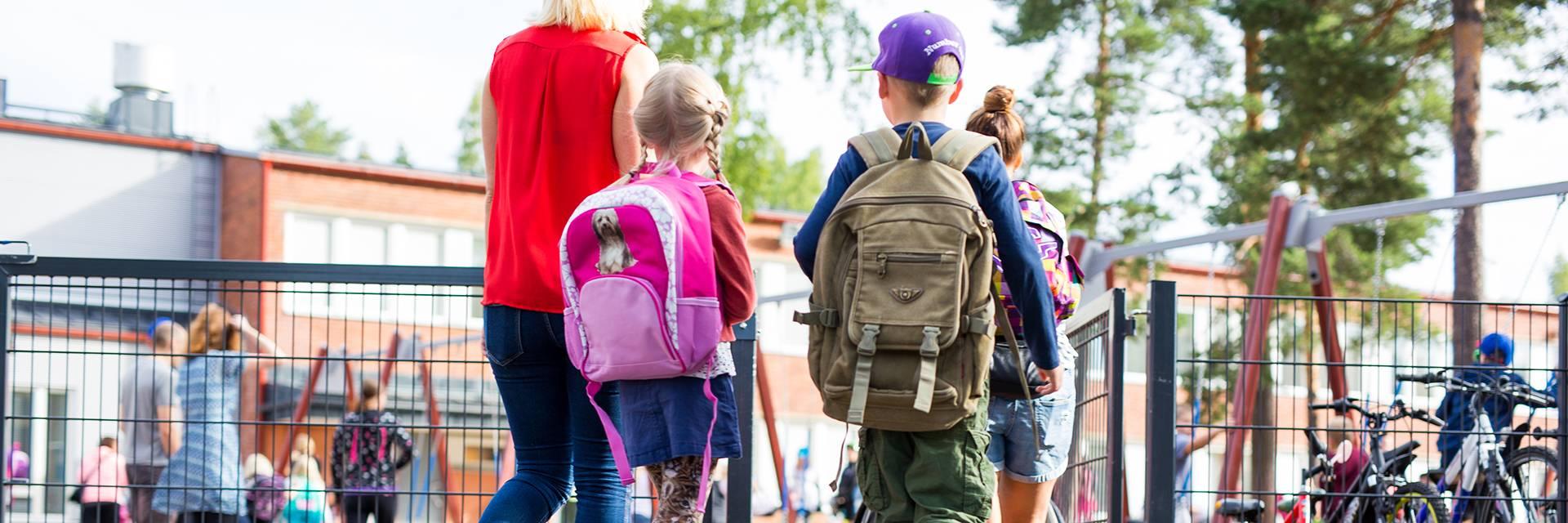 Lapset kävelee koulun pihaan