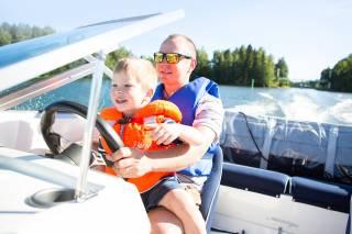 mies ja poika ajavat yhdessä veneellä