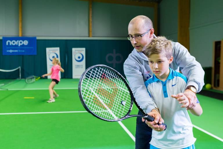 Poika harjoittelee tennistä opettajan kanssa