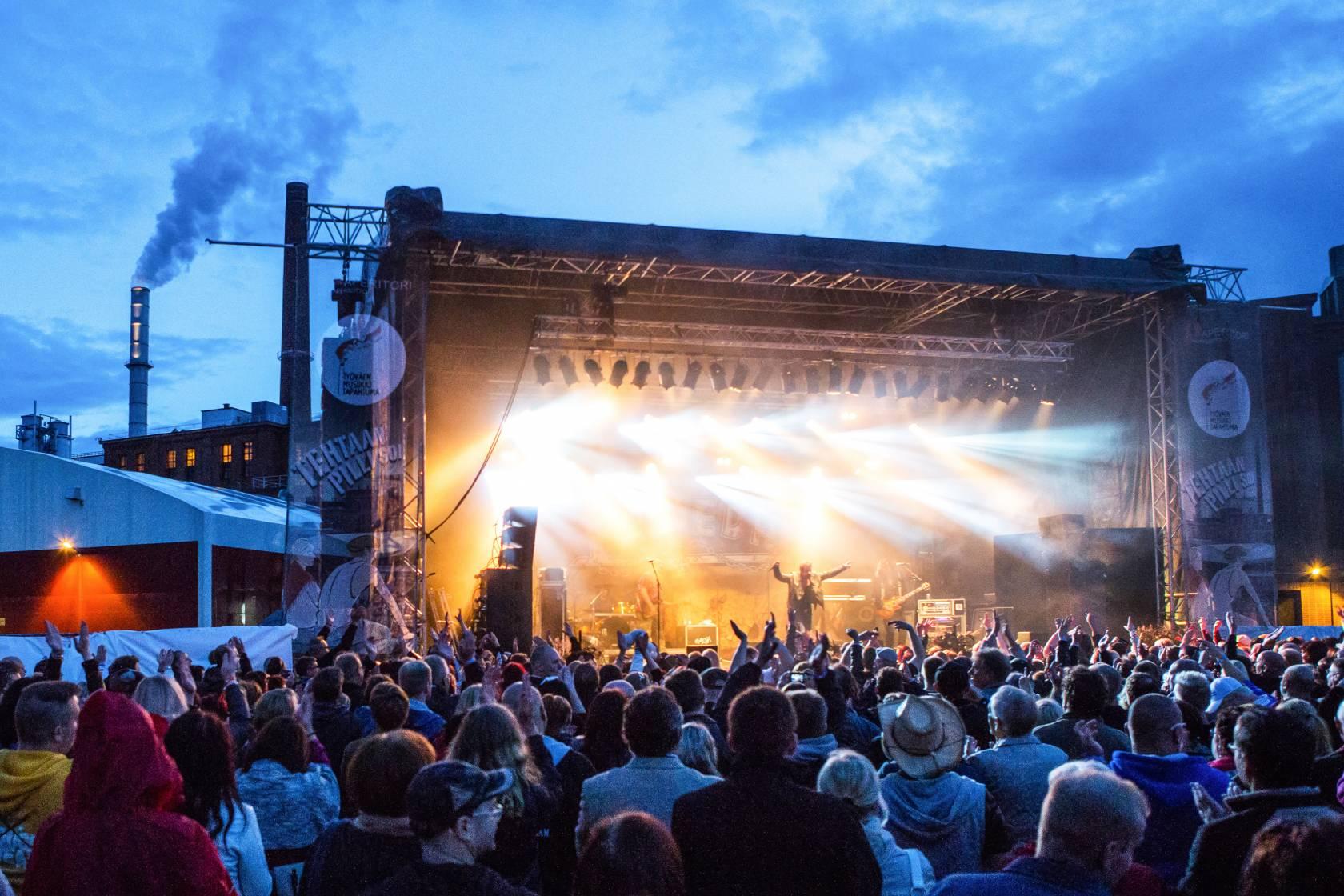 Esiintyjä lavalla yleisön edessä Työväen Musiikkitapahtumassa.