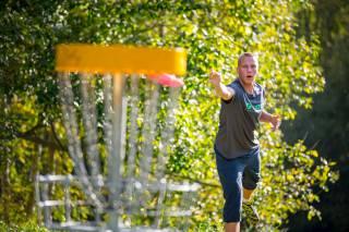 Miehet pelaavat frisbeegolfia.