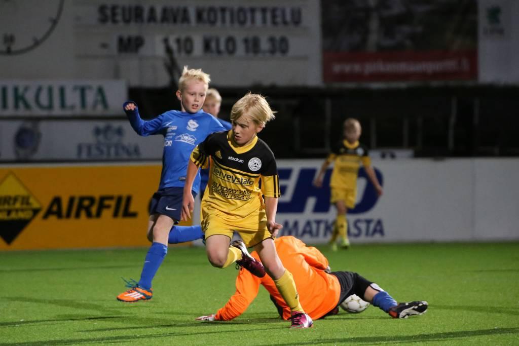 Pojat pelaavat jalkapalloa.