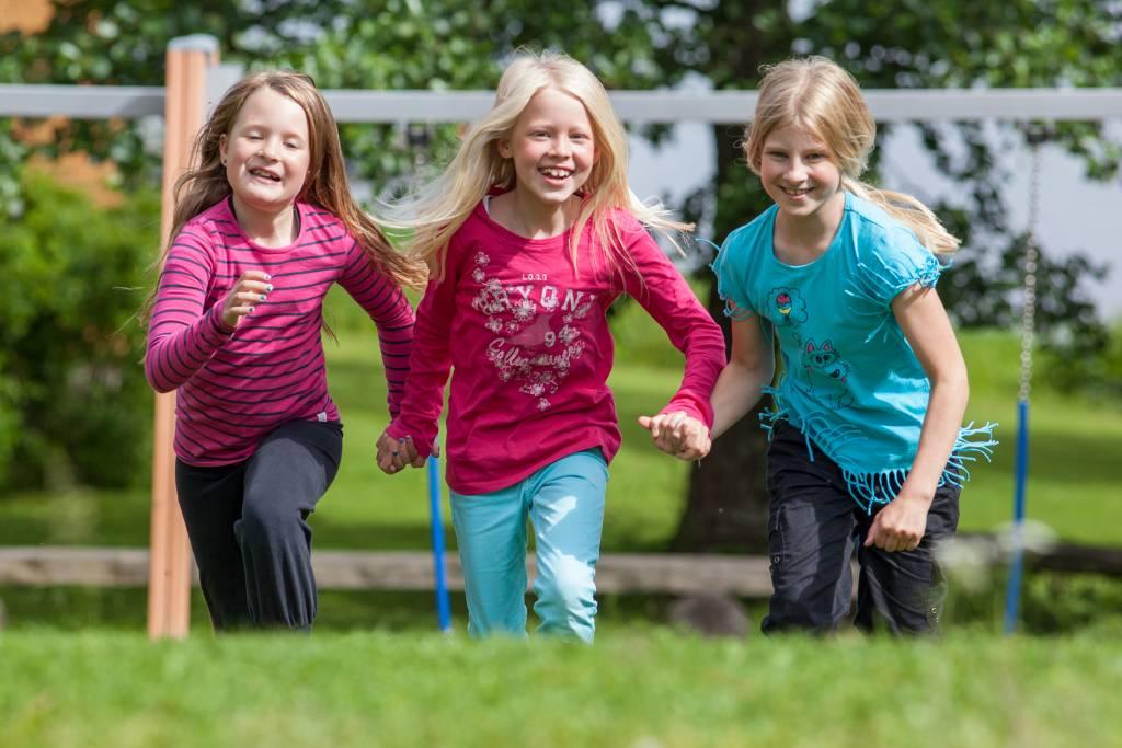 Lapset juoksevat ulkona puistossa käsikädessä
