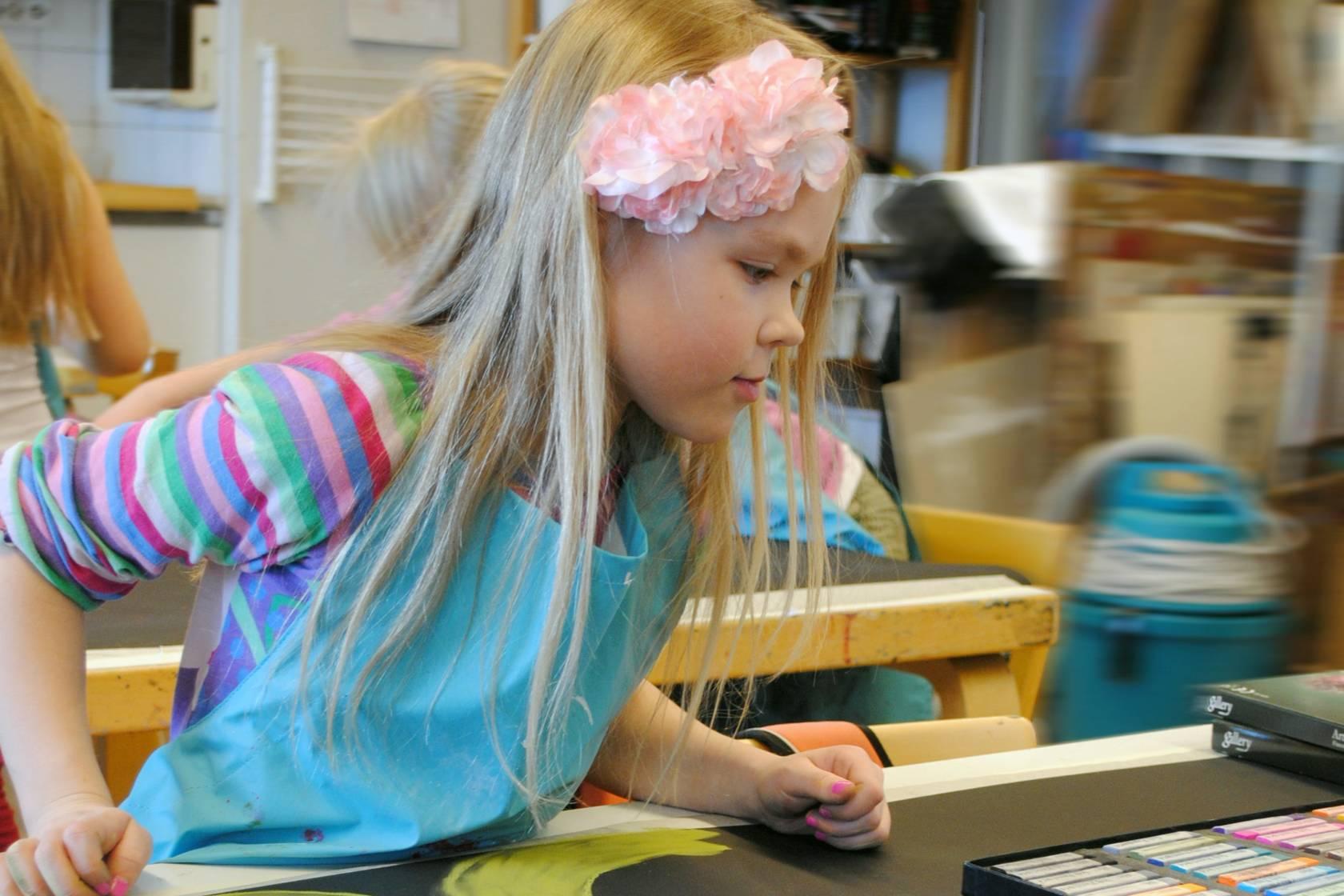 Lapsi piirtää pastelliliiduilla
