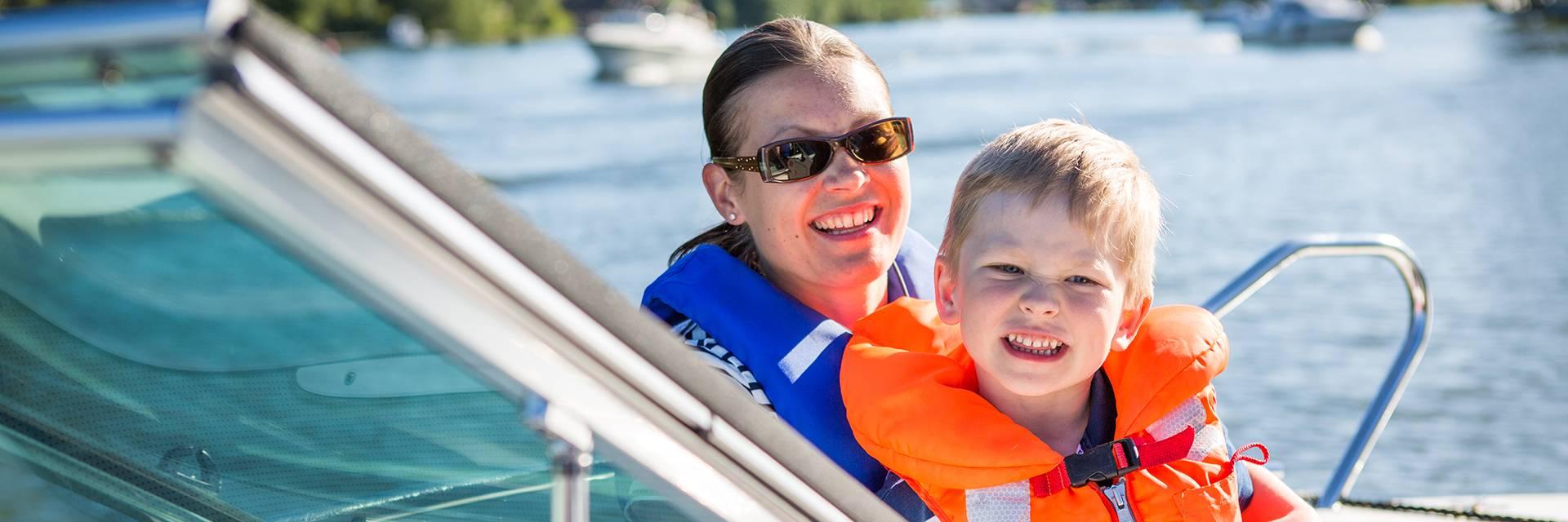 Nainen ja poika istuvat veneessä