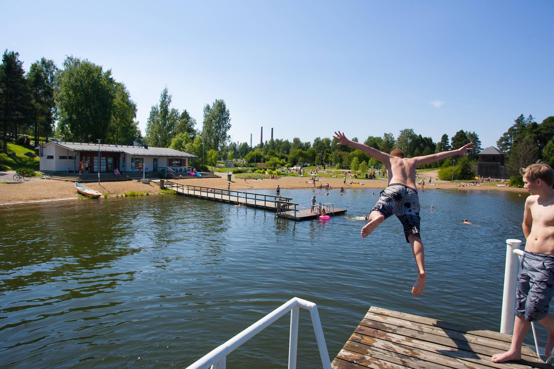Mies hyppää uimahypyn veteen Apianniemen uimarannan laiturilta