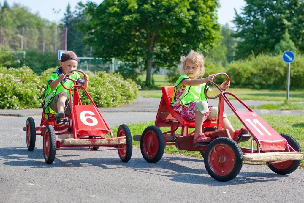 Kaksi lasta ajaa polkuautoilla liikennepuistossa