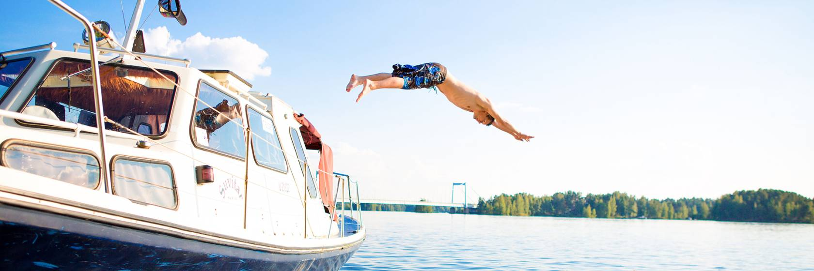 Mies hyppää veneestä veteen