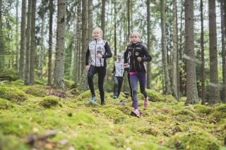 Lapset suunnistavat metsässä