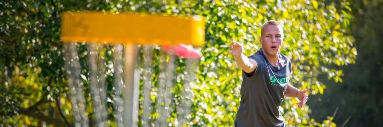 Mies heittää frisbeegolfkoriin frisbeetä