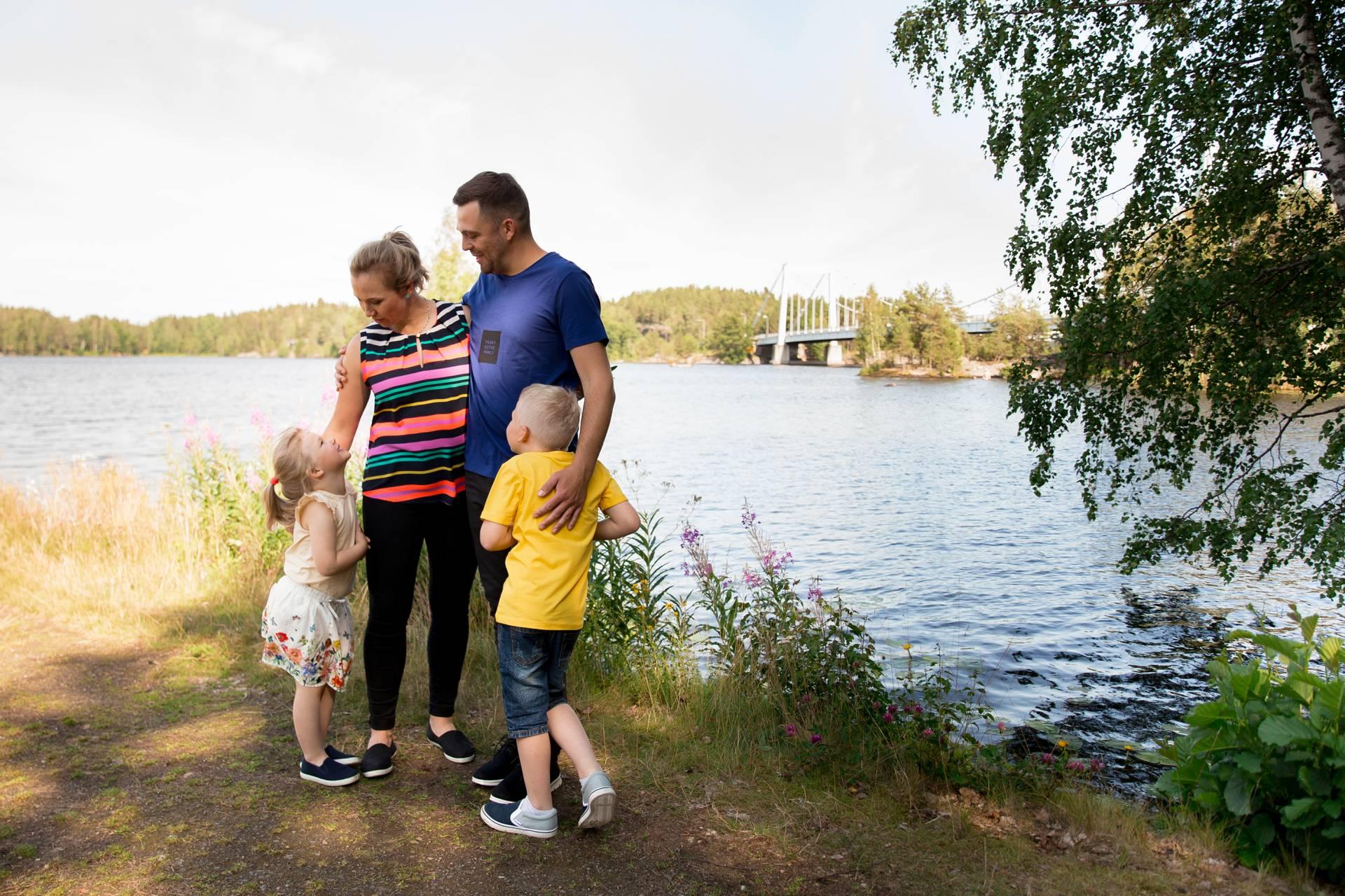 Perhe rannalla taustalla Sääksmäen silta