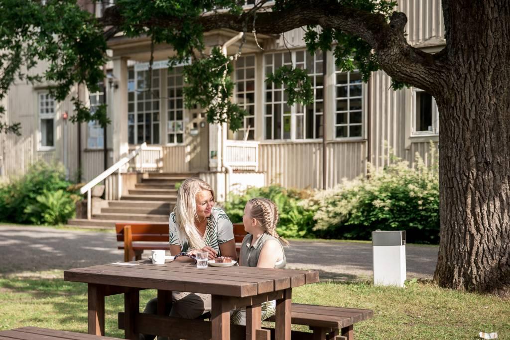 Nainen ja tyttö istuvat Voipaalan kartanokahvilan ulkopöydän ääressä