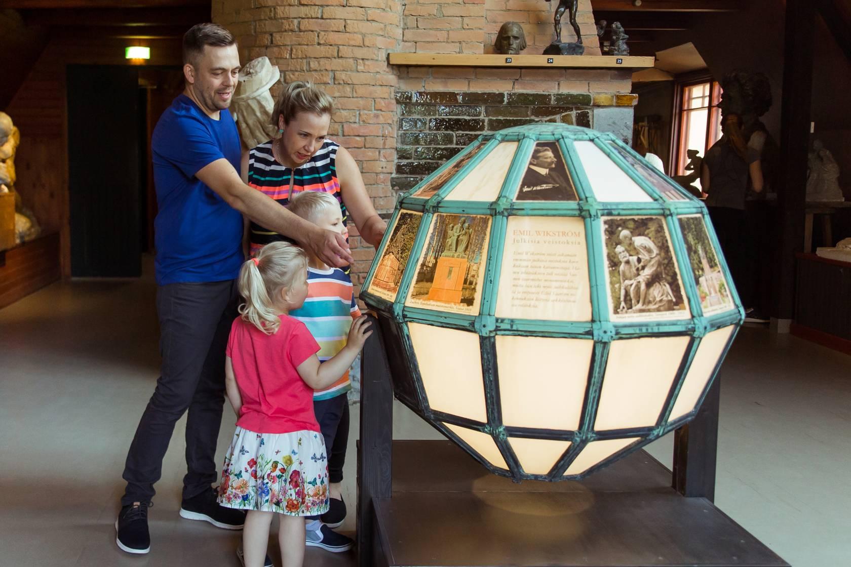 Perhe lukee tietoja teoksesta Visavuoren ateljeessa
