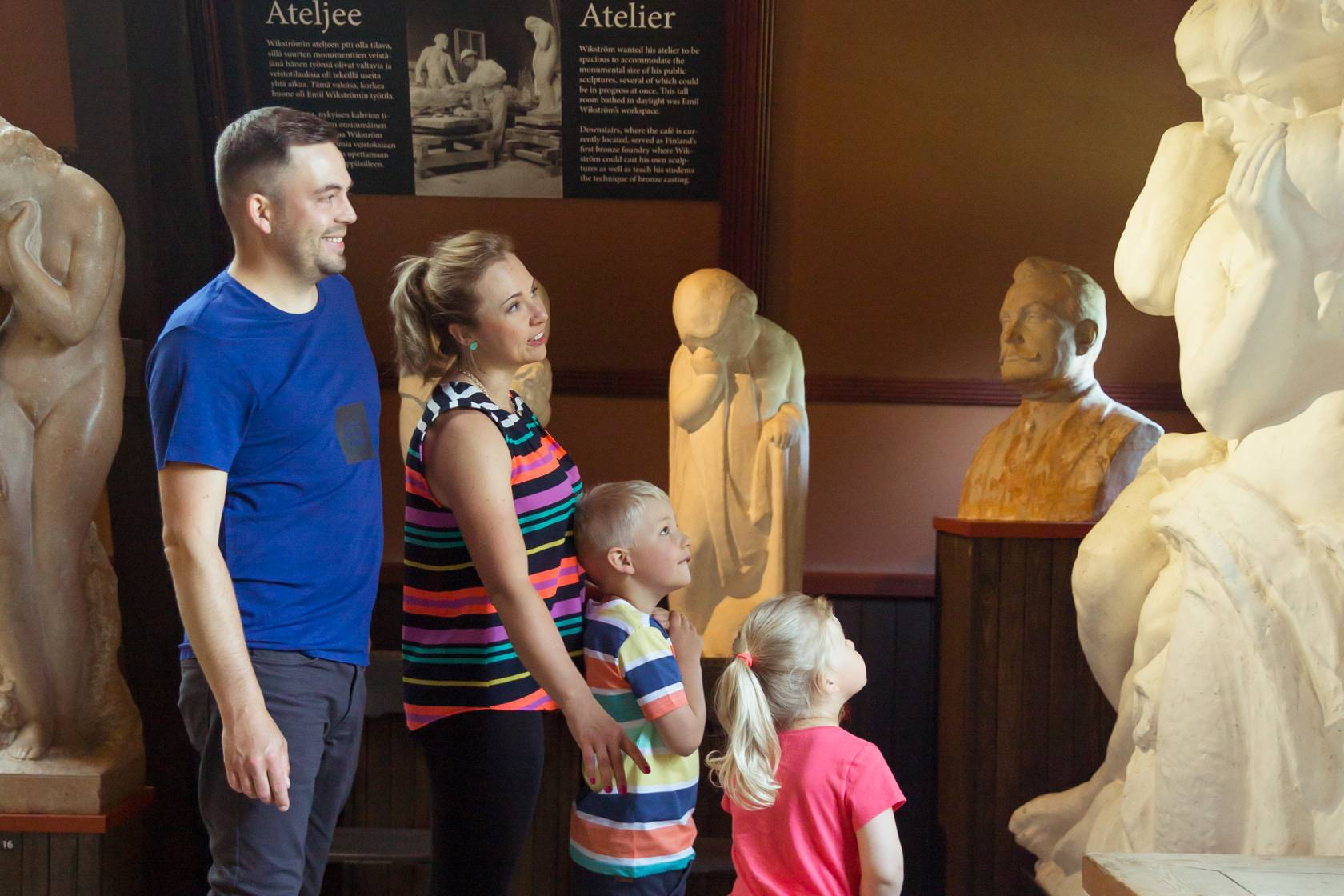 perhe katselee taidetta Visavuoren ateljeessa