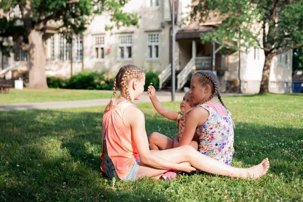 Lapset istuvat nurmikolla Voipaalan kartanon edustalla