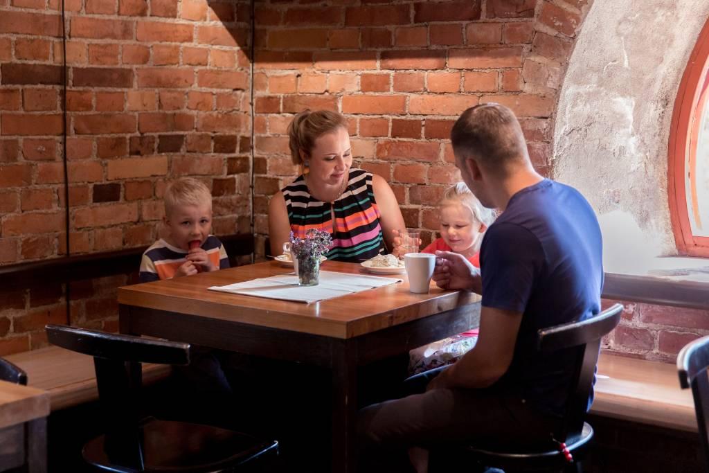 Perhe istuu Visavuoren museokahvilan pöydän ääressä