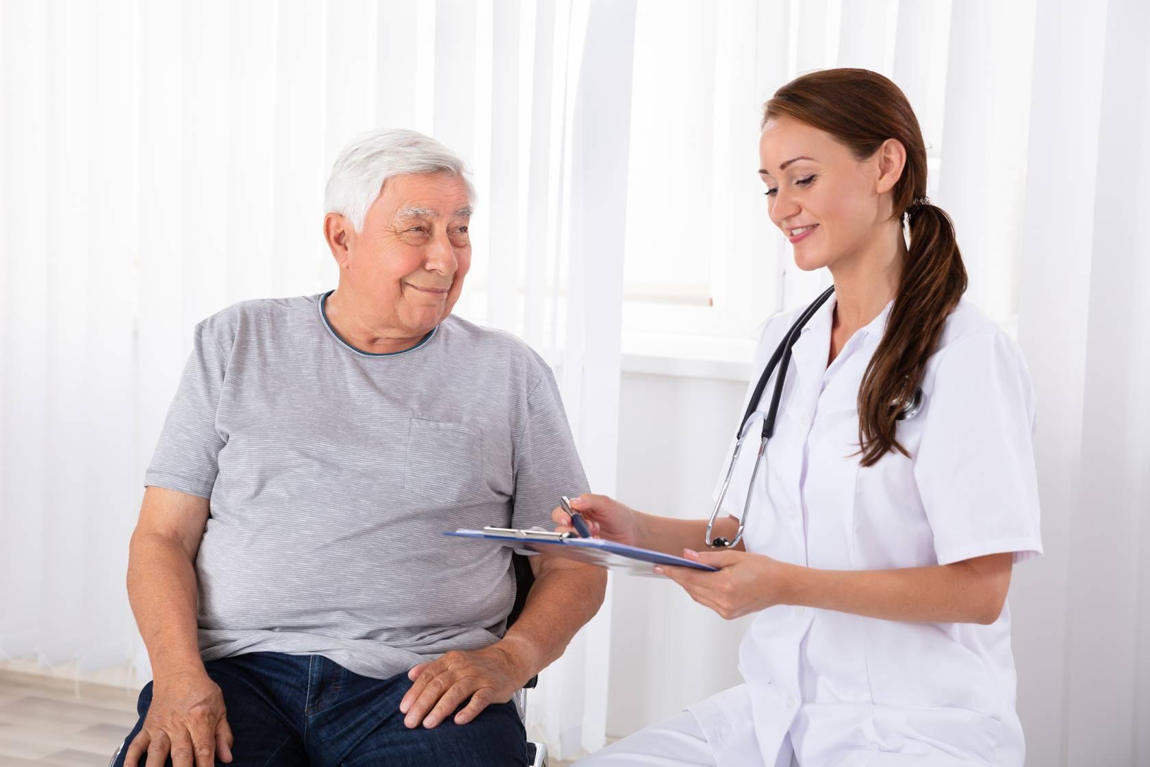 Lääkäri haastattelee ikäihmistä.