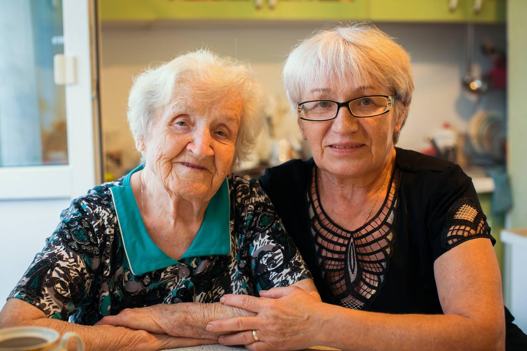 Vanhempi ja nuorempi ikäihminen istuvat vierekkäin