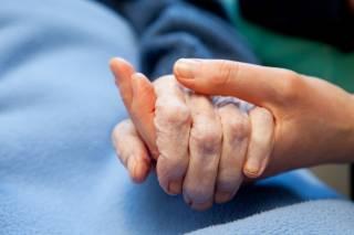 Nuorempi ja vanhempi henkilö pitävät toisiaan kädestä