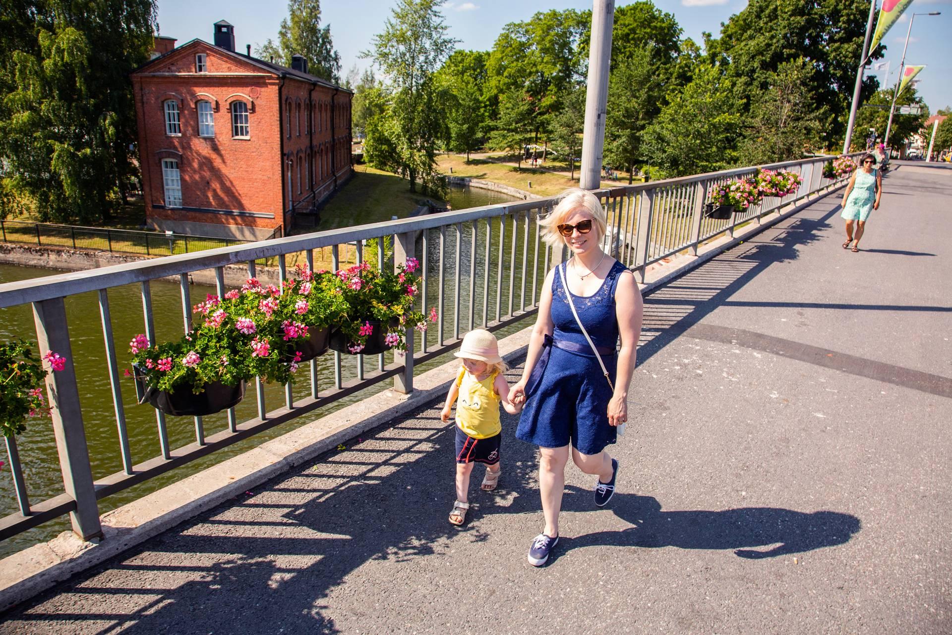 Nainen ja tyttö kävelee Valkeakosken keskustassa sillalla Myllysaaren edustalla