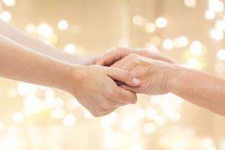 Nuorempi ja vanhempi pitävät kädestä toisiaan