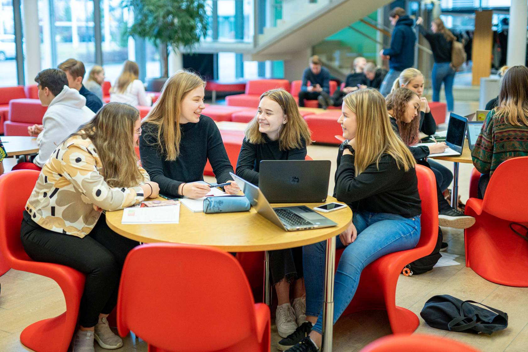 Tyttöryhmä Tietotien lukion aulassa punaisilla nojatuoleilla.