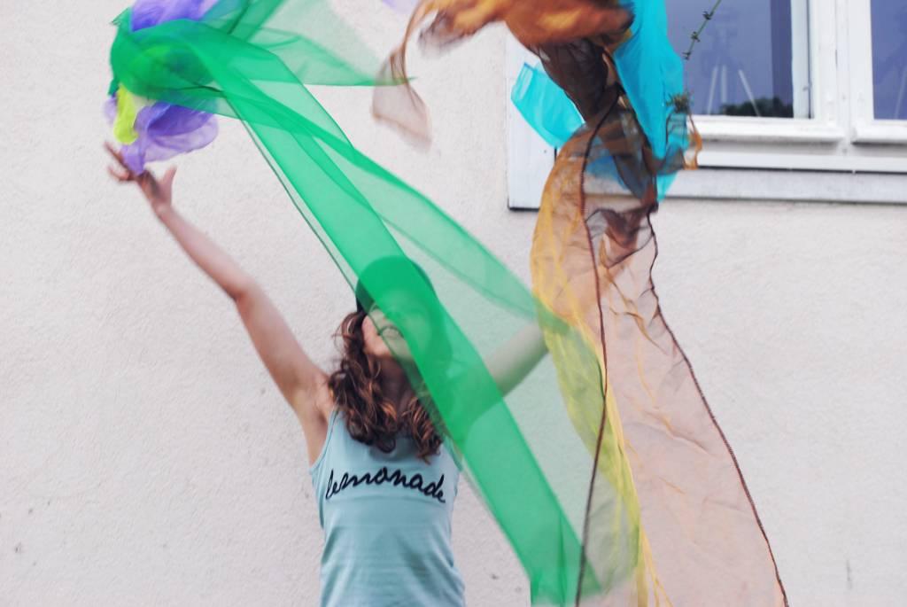 Kuvassa tyttö heiluttelee värikkäitä huiveja Emilin kesäleirillä