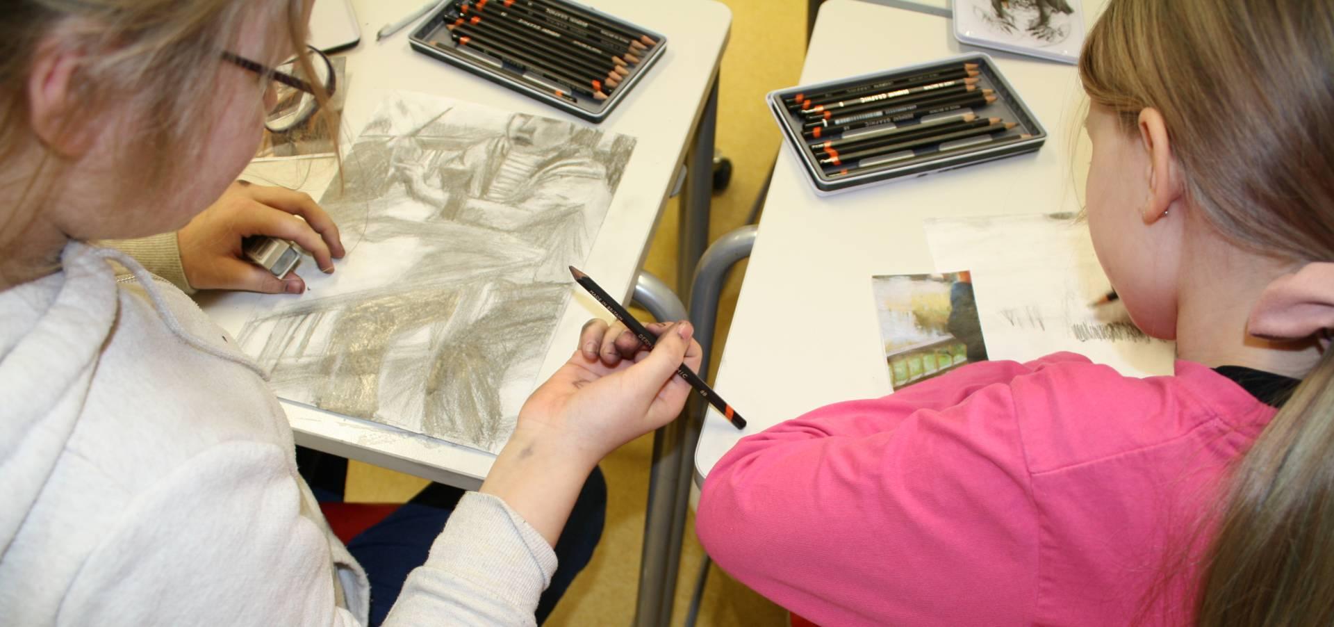 lapsia piirtämässä lyijykynällä