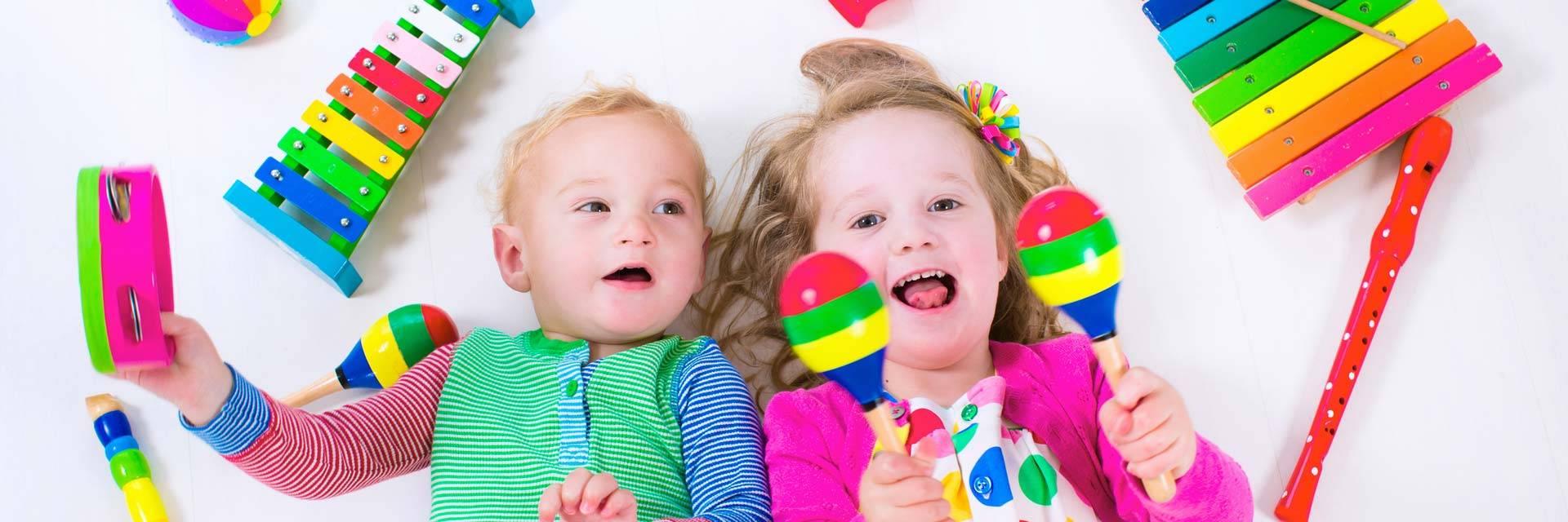 Kaksi lasta soittaa värikkäillä musiikki-instrumenteilla