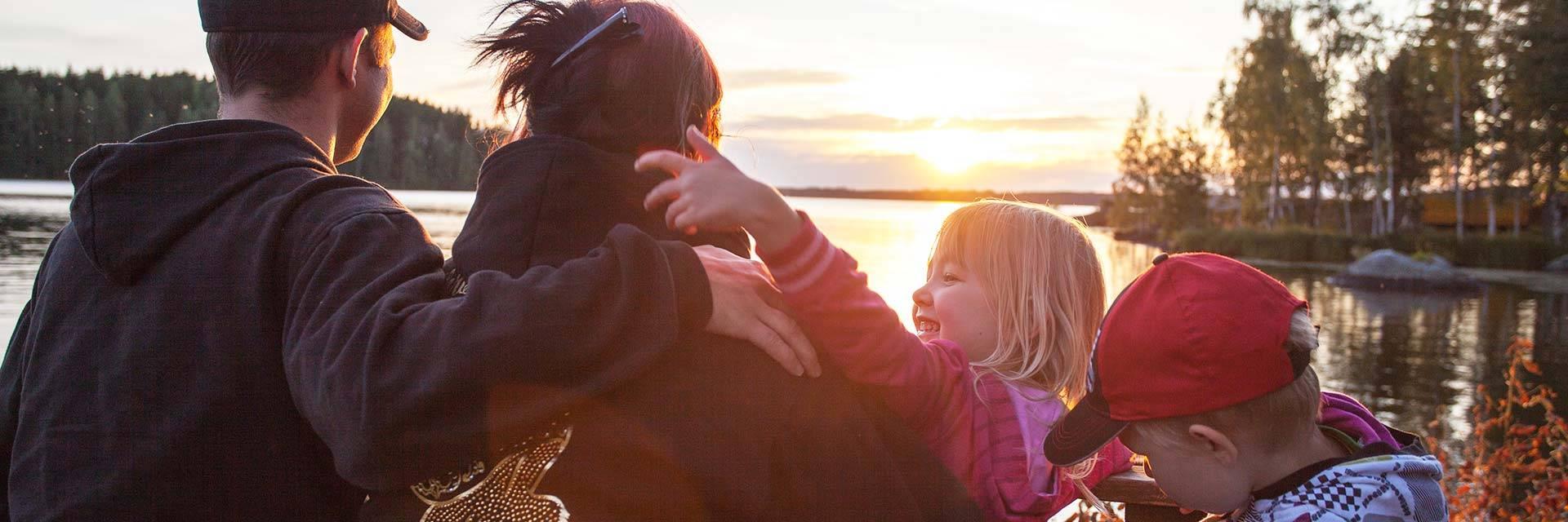 Äiti, isä ja kaksi lasta istuu järven tannalla auringon laskiessa