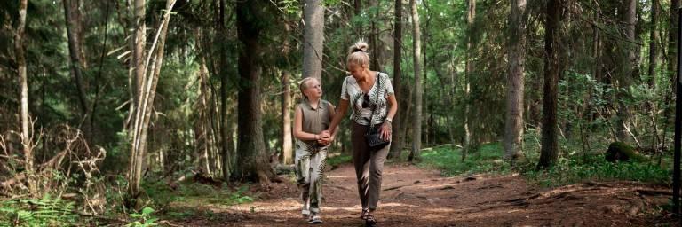 Nainen ja tyttö kävelemässä Rapolanharjun metsäpolulla