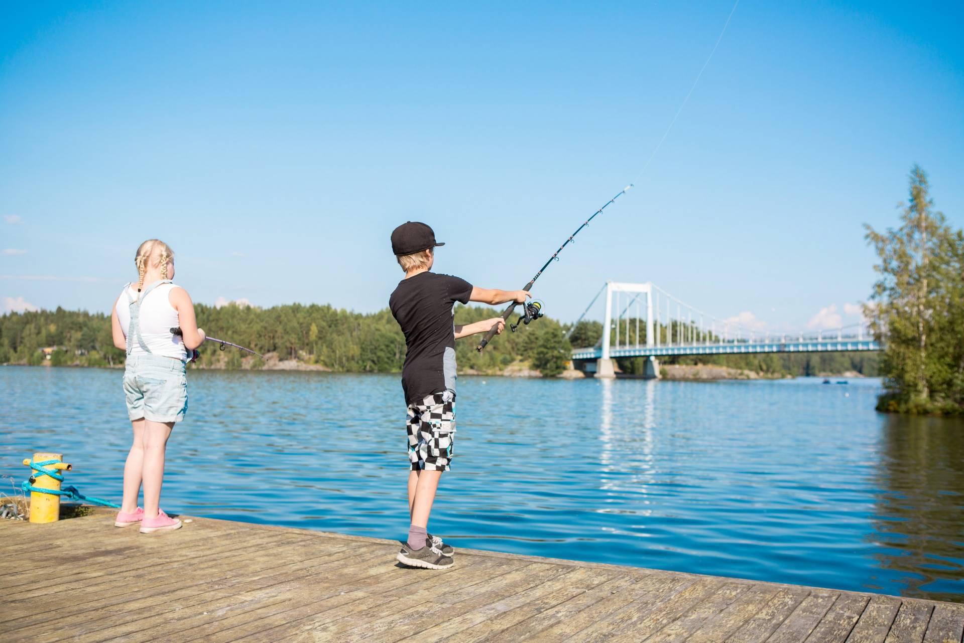 Tyttö ja poika kalastavat laiturilla