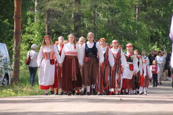 Nuoria neitoja kansallispuvuissa helkajuhlakulkueessa.