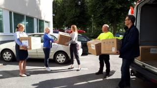 UPM:n työntekijät ojentavat maskilaatikoita Tarja Laineelle.