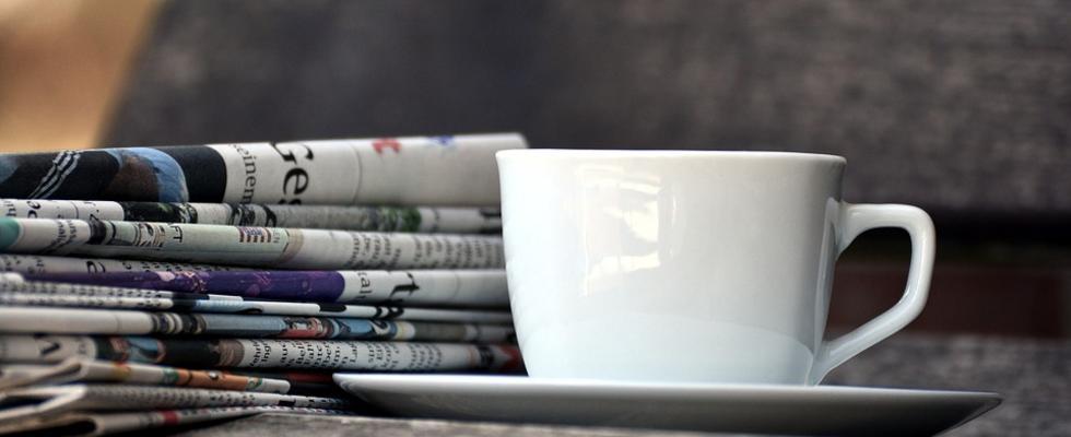 Kahvikuppi ja nippu sanomalehtiä.