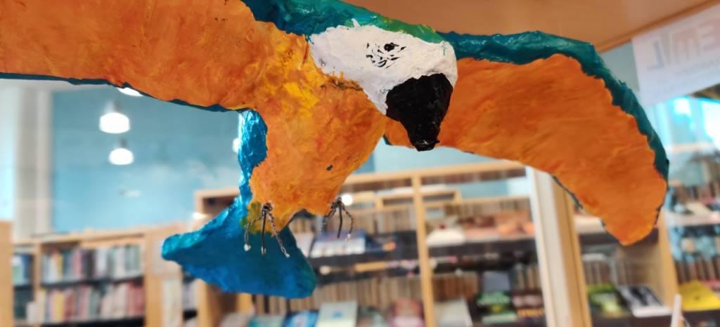 Paperimassasta tehty värikäs lintu, oppilastyö.
