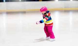 Lapsi luistelee jäähallissa.