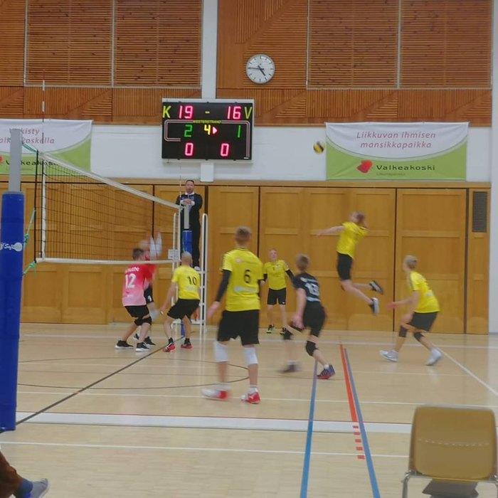 Miehet pelaavat lentopalloa.