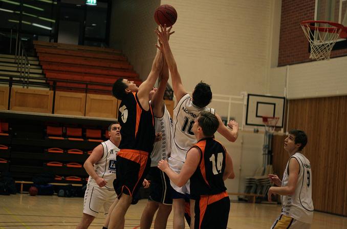 Miehet pelaavat koripalloa.