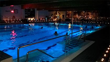 Tunnelmallista uintia kynttilöiden valossa uimahallissa.