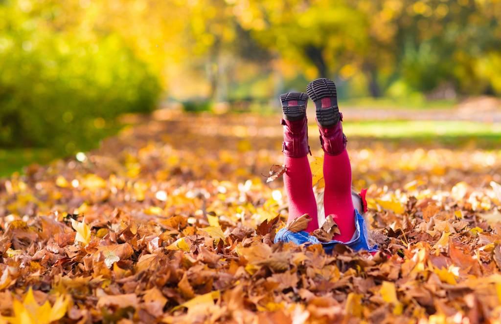 Lapsi leikkii puistossa värikkäissä syksyn lehdissä.