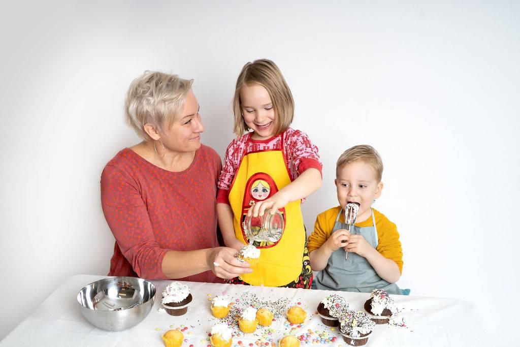 Nainen ja kaksi pikkulasta leipovat.