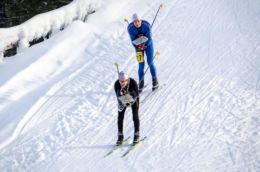 Kaksi miestä laskee mäkeä hiihtosuksilla