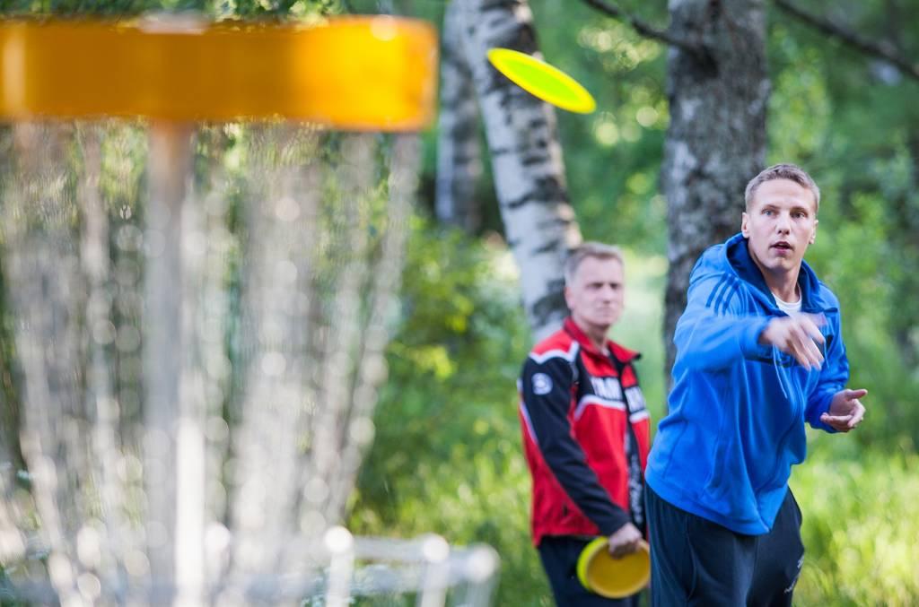 Mies heittää frisbeetä koriin ja toinen mies seuraa taustalla