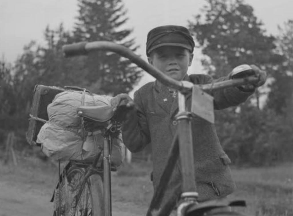 Vanha kuva pyörää taluttavasta pojasta.
