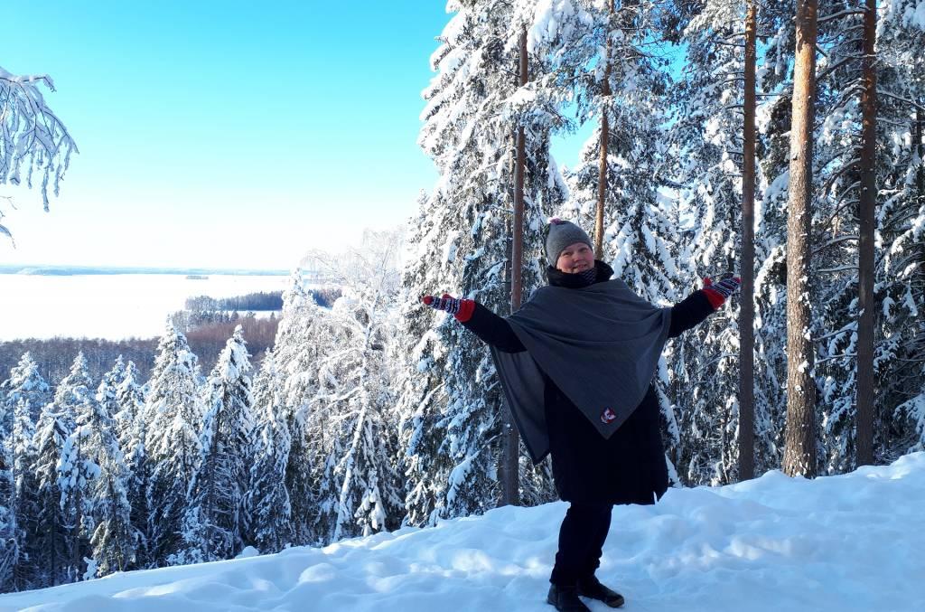 Ihminen on levittänyt kätensä talvisen harjumaiseman edustalla.