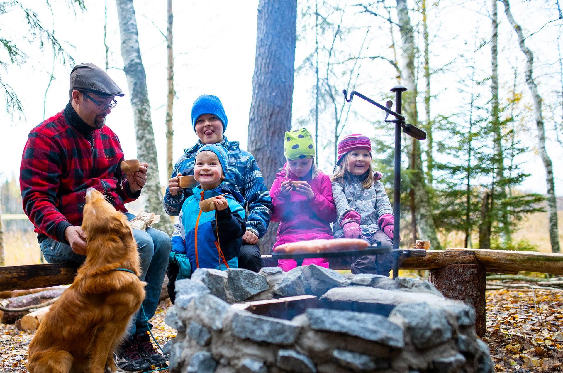 Perhe grillaa makkaraa nuotiopaikalla.