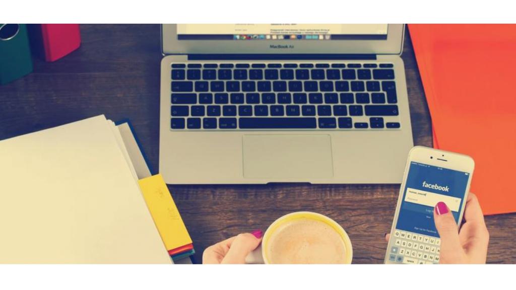 Tietokone ja naisen kädessä kahvikuppi sekä kännykkä.